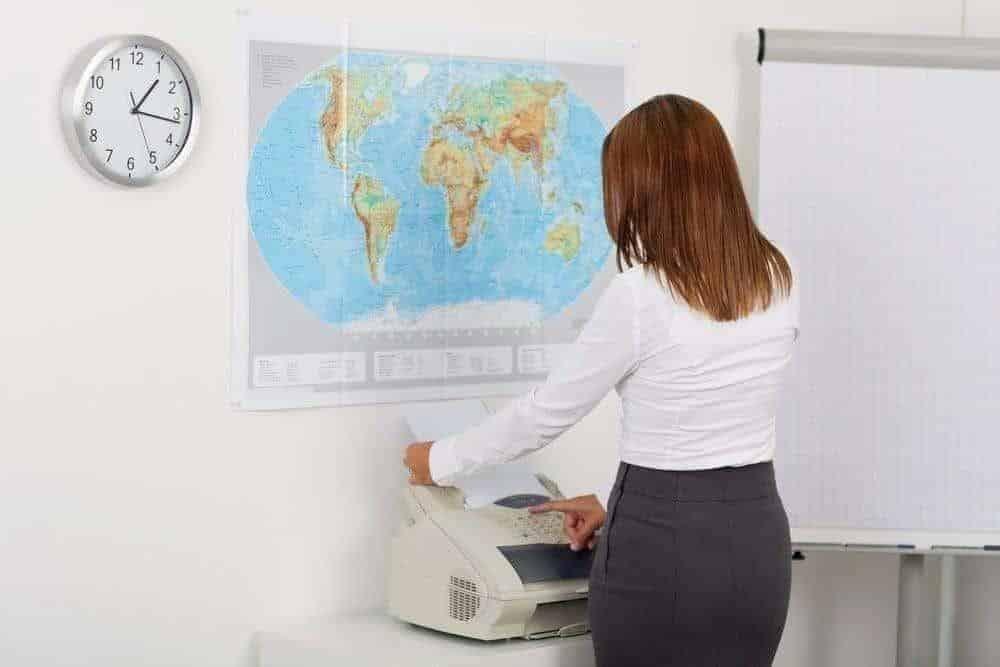 businesswoman using efax mailbox machine in office